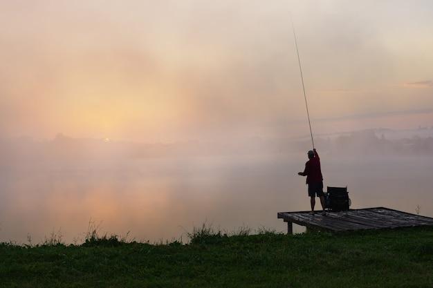 朝の空を背景に夜明けの漁師で釣り