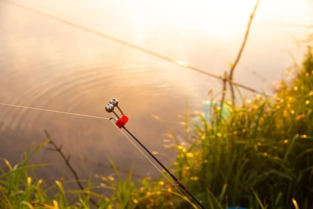 Рыбалка на туманном озере рано утром сразу после золотого восхода солнца. рыбный колокол крупным планом.