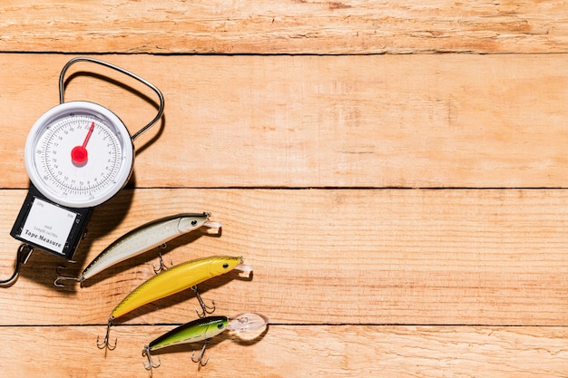 Рыболовные приманки с весами на деревянном столе