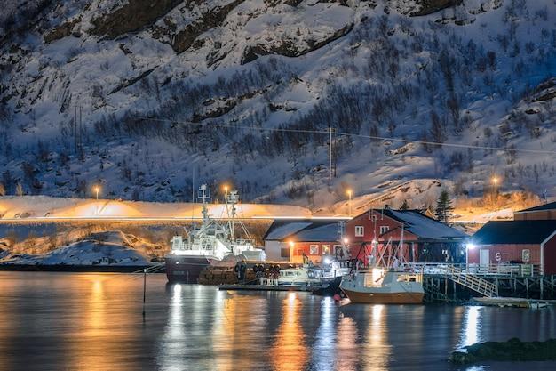 ノルウェー、ロフォーテン諸島の海岸線にある照らされた漁村のドックに停泊している漁船