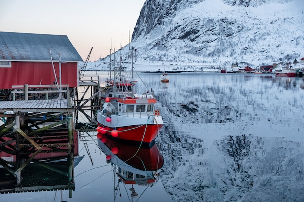 Fishing boat anchored on pier with red village in lofoten islands