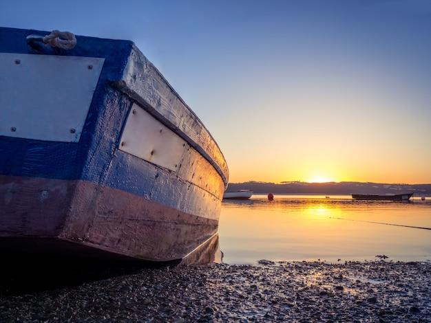 美しい夕日と川で釣りボート