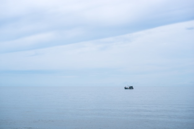 Fishing boat in the calm sea ocean and blue clear sky background.