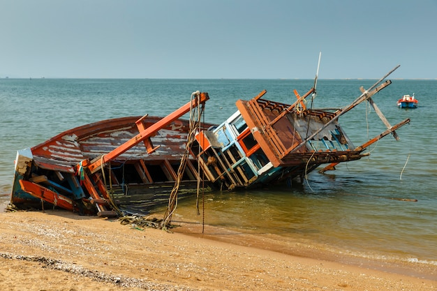 Fishing boat crashed lies on its side near the shore