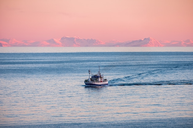 Fishing boat cruising on arctic sea to fish at sunset in winter