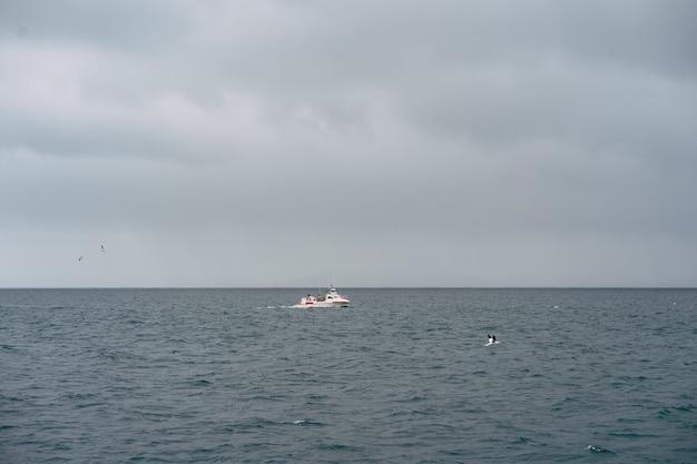 Рыбацкая лодка плывет в атлантическом океане недалеко от исландии