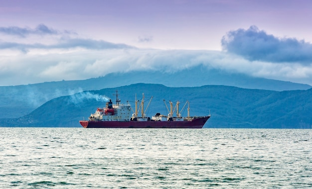 Fishing boat in gray morning on pacific ocean off the coast of the kamchatka peninsula