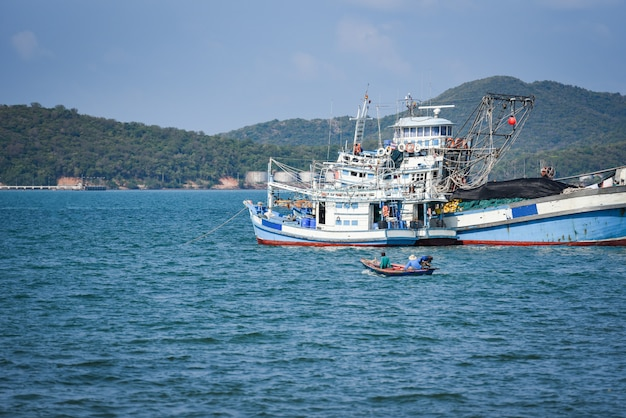 Fishing boat at harbor in the ocean sea and mountain in thailand