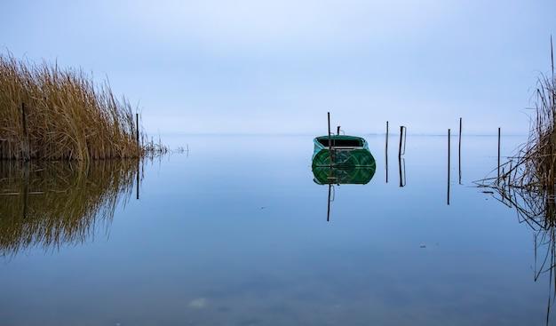 Рыбацкая лодка в озере до восхода солнца. красивый спокойный пейзаж
