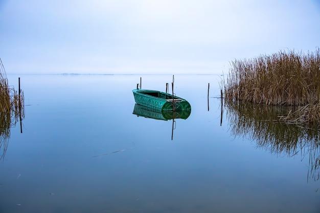 日の出前の湖での漁船