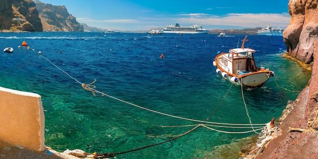 Рыбацкая лодка, моторные лодки и круизные лайнеры в меса ялос, старый порт фиры, санторини, в солнечный день, греция. панорама