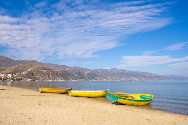 Рыбацкая лодка на песчаном пляже. гора на побережье Premium Фотографии