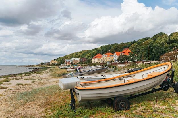 Рыбацкая лодка на пляже, лодка на берегу моря, старая гребная лодка на пляже.