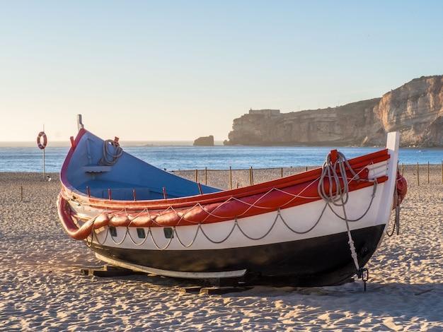 Рыбацкая лодка на пляже назаре в португалии в дневное время