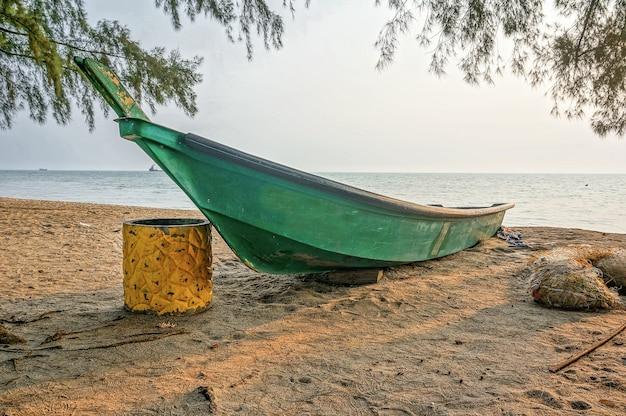 Рыбацкая лодка на пляже при восходе солнца