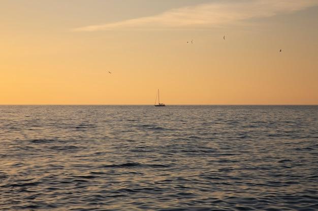 地平線上の漁船、海に沈む夕日。穏やかな海、珊瑚の空、夜釣り