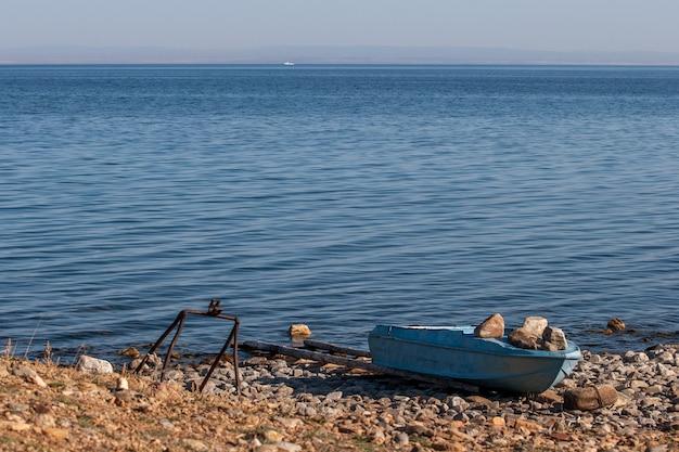 青いバイカル湖の岸にある漁船
