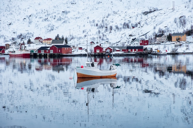 Fishing boat sailing reflection on arctic sea with scandinavian village