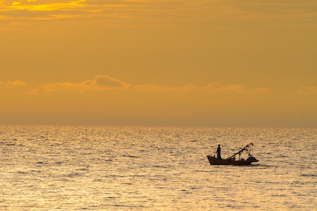 Fishing boat in sunset.