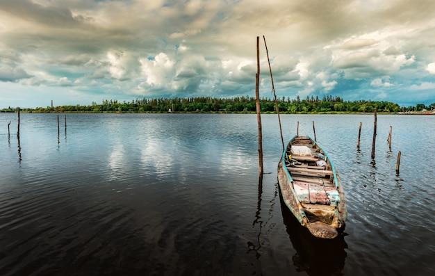 Рыбацкая лодка с видом на пейзажную природу в небе и тучу и реку в сезон штормовых дождей
