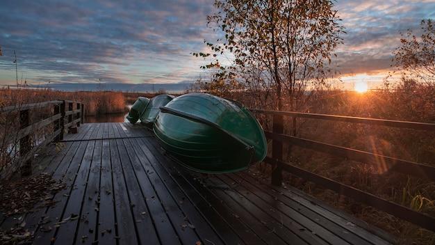 ロシアのレニングラード地域にあるキャンサーレイクス自然保護区の木製の桟橋で漁船が乾燥しています。夜明けの秋