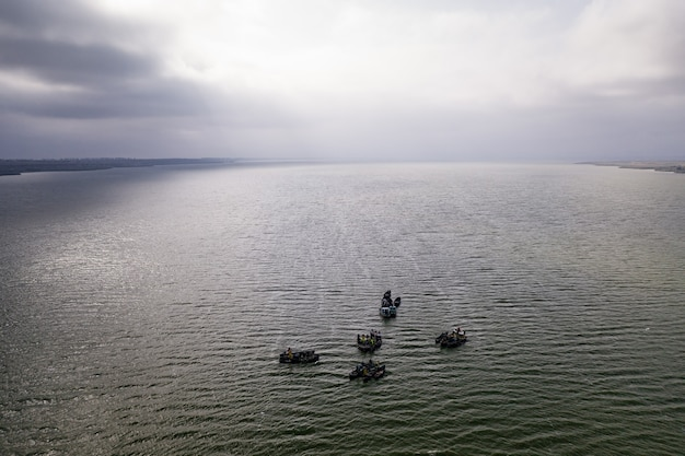 Fishing boats, floating the calm waters and going for fishing under a sky with clouds