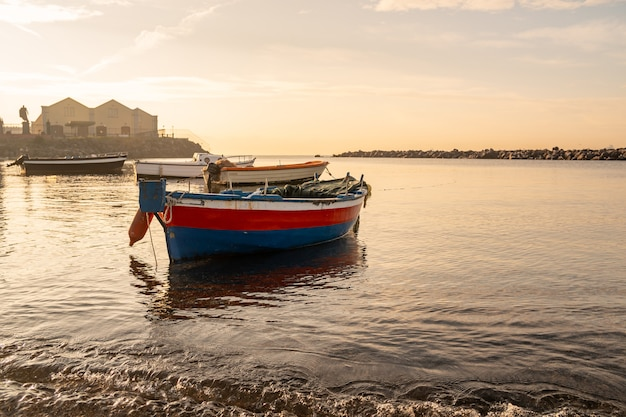 Рыбацкие лодки плывут на берегу средиземного моря. италия. морской пейзаж.