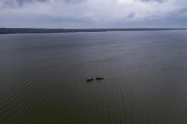 낚시 보트, 잔잔한 물에 떠 다니고 구름이있는 하늘 아래에서 낚시하기