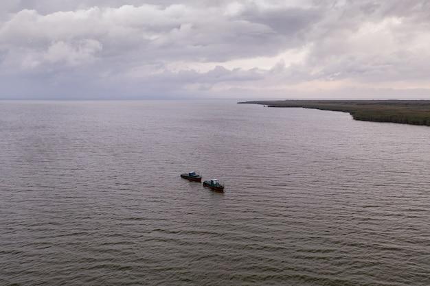穏やかな海に浮かぶ漁船、雲のある空の下で釣りに行く