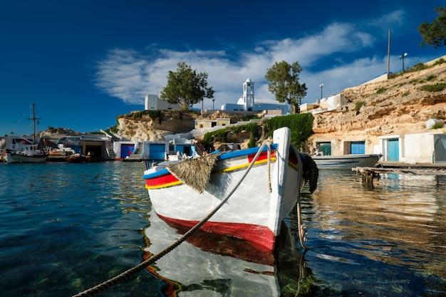 Fishing boats moored in crystal clear turquoise sea water in harbour in greek fishing village of mandrakia, milos island, greece.