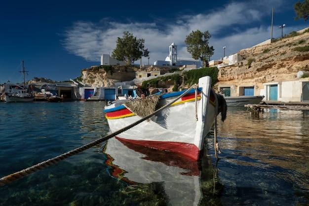 ギリシャのミロス島、マンドラキアのギリシャの漁村にある港の澄んだターコイズブルーの海の水に係留された漁船。