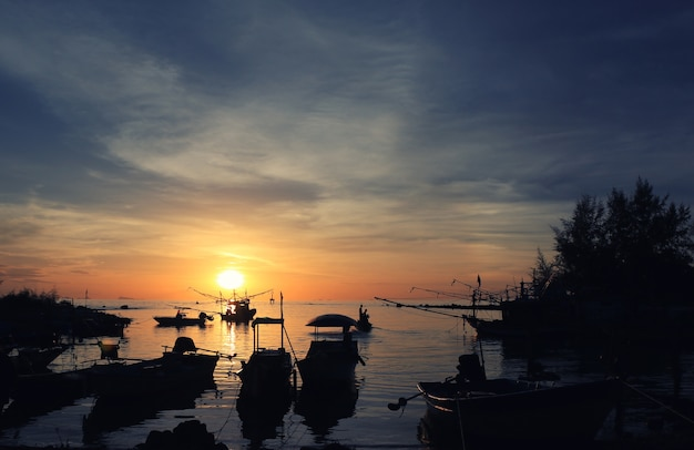 Fishing boats on the seashore sunset time silhouette
