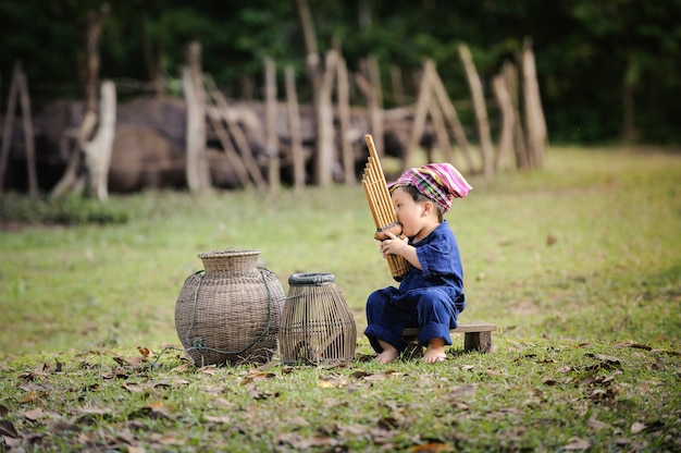 Fishing boy sit and blow reed organ in the farm ,fell relaxed after fishing form the river