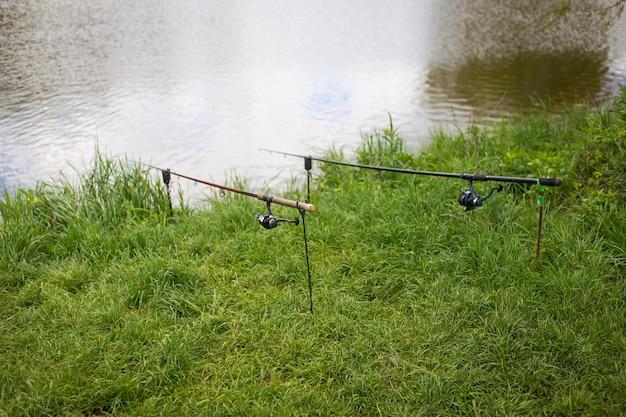 釣り、釣り竿は池の岸にあるスタンドにあります。屋外レクリエーション、夏、休暇、休日。