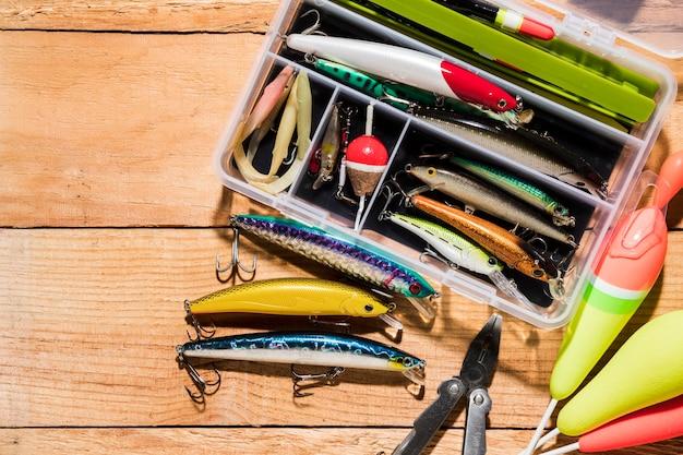 釣りフロートと木製の机の上のペンチでルアー