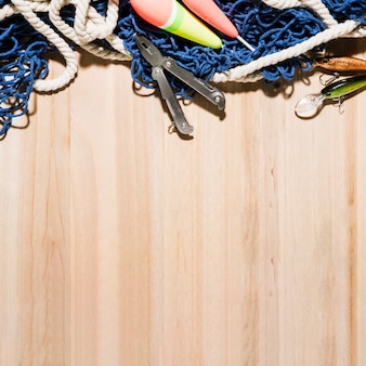 Fishing float; pliers; fishing lure and fishing net on wooden surface