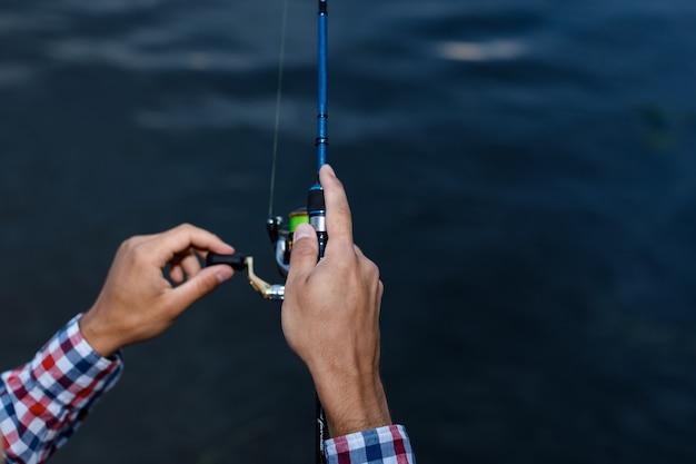 日没時に川で釣り。釣り竿のホイールのクローズアップで釣り男