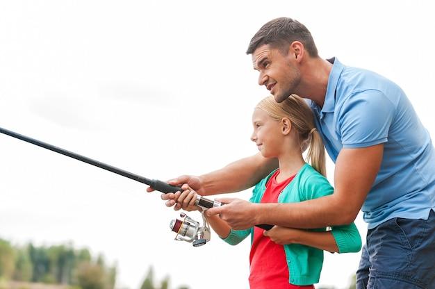 Рыбалка - это весело. веселый отец и дочь вместе ловят рыбу и улыбаются