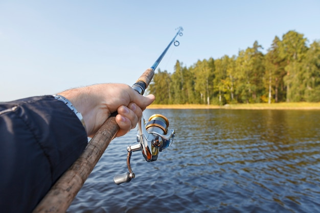 Fishing on a lake. fishing rod with a reel in hand