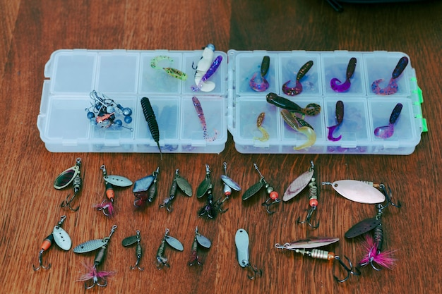 Fishing lures with boxes on wooden desk