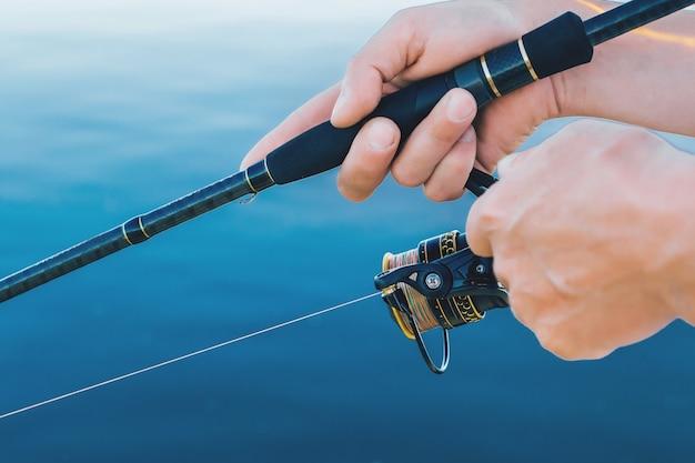 Ловля рыбы. человек в руках держит спиннинг с катушкой.