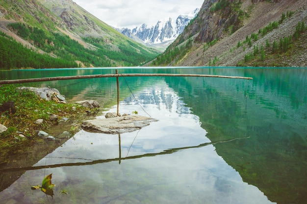 Fishing in mountain lake overlooking glacier. rich vegetation in highlands. giant wonderful mountains reflected in shiny water surface. fishing lift. atmospheric amazing landscape of majestic nature.