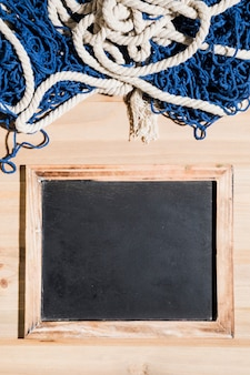 Fishing net over the blank blackboard over the wooden surface