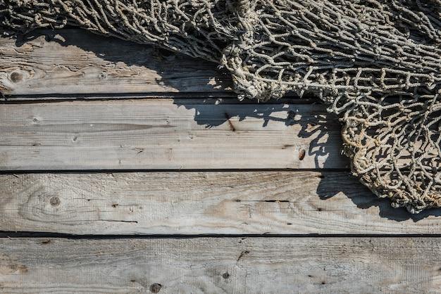 나무 벽에 오래 된 네트워크 낚시, 나일론 로프로 짠 어부 민속의 그물 질감 낚시