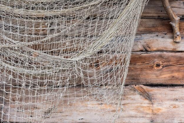 木製の壁に古いネットワークを釣り、漁師の人々の網のテクスチャを釣ります