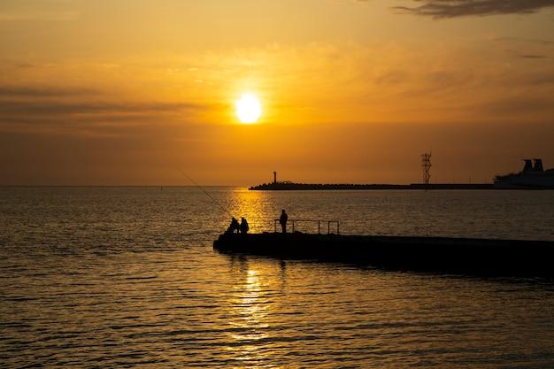 바다에서 낚시. 남자는 여름에 일몰 저녁에 물고기