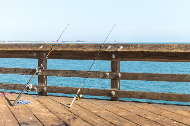 Fishing poles leaning on a rail on a pier in ventura los angeles california