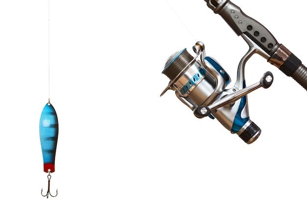 Рыболовная катушка и ложка, изолированные на белом фоне