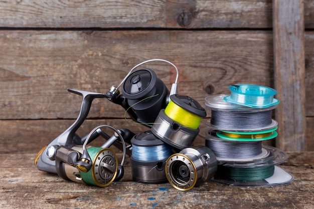 Fishing reels and spoole with line on wooden table