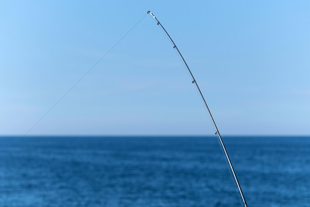 Fishing rod against blue ocean or sea background